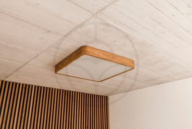 Wooden square ceiling LED lamp with high-end technology. Contrast between the cold raw concrete and pleasant warmth of wood. Nordic design.