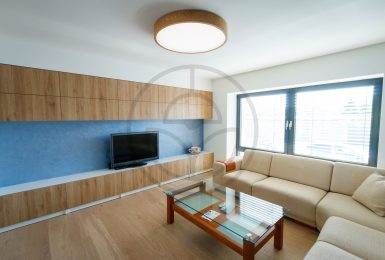 Trilum's woodLED Round luminaire is main light source in pleasant living room. Wooden lamp made of oak wood fits vell into the minimalist interior design.